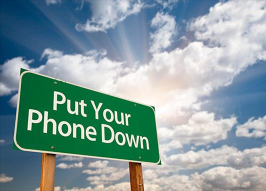 """A green road sign with white text that says """"put your phone down"""" against a blue sky with clouds"""