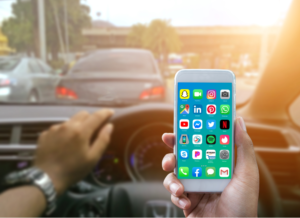 Unidentified driver with one hand on the wheel and the other hand holding a phone with lots of distracting apps on it